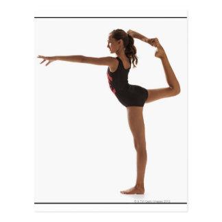 Gymnaste féminin (12-13) équilibrant sur une jambe carte postale