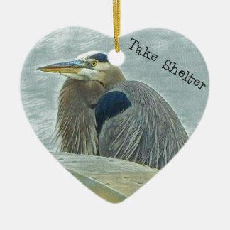 héron bleu abritant du vent derrière le bateau sur ornement cœur en céramique