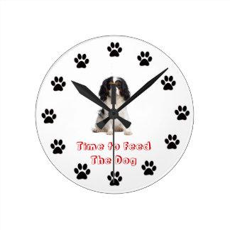 Heure d'alimenter au chien l'épagneul cavalier du  horloge murale