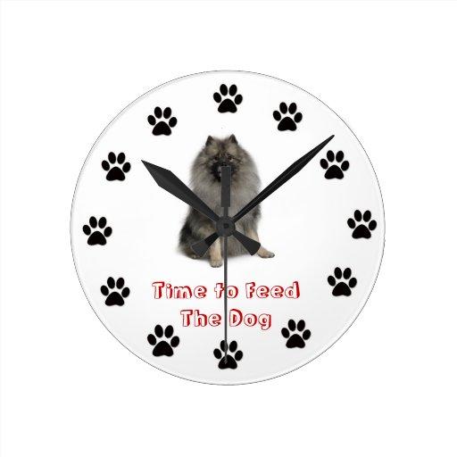 Heure d'alimenter le keeshond d'horloge de chien