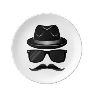 Hippie frais avec la moustache, le casquette et assiettes en porcelaine