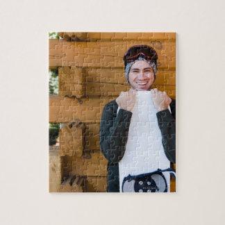 Homme de sourire posant avec le surf des neiges en puzzle