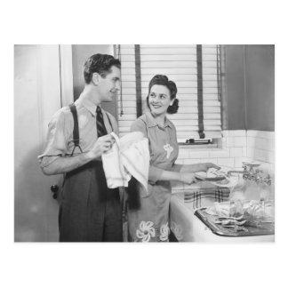 Homme et femme faisant des plats carte postale