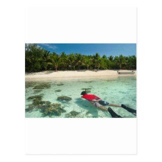 Homme naviguant au schnorchel outre d'une île cartes postales