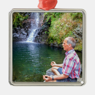 Homme s'asseyant sur la roche méditant près de la ornement carré argenté