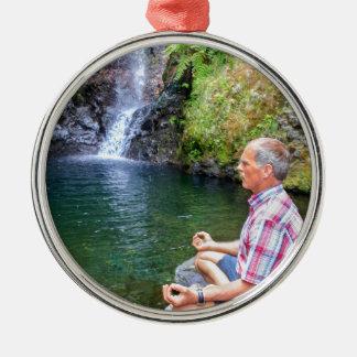 Homme s'asseyant sur la roche méditant près de la ornement rond argenté