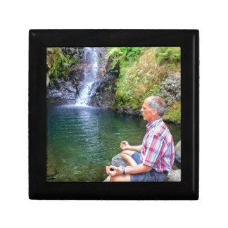 Homme s'asseyant sur la roche méditant près de la petite boîte à bijoux carrée