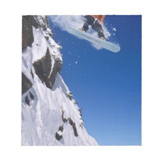 Homme sur un surf des neiges sautant outre d'une c blocs notes