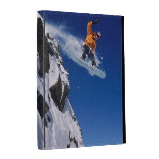 Homme sur un surf des neiges sautant outre d'une coque folio iPad