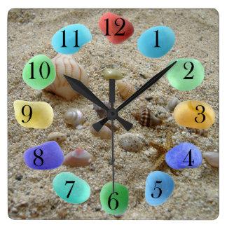 Horloge Carrée Coquillages sur le sable de plage avec le verre de