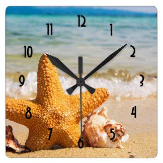 Horloge Carrée Étoiles de mer et coquillages sur la plage