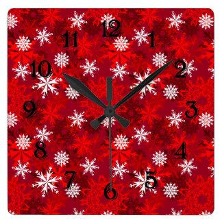 Horloge Carrée Flocons de neige sur l'arrière - plan rouge