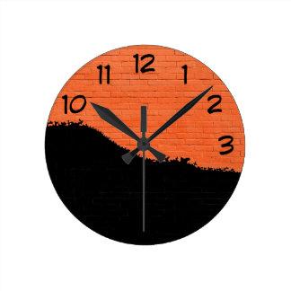 Horloge Ronde Mur de briques orange avec la peinture noire