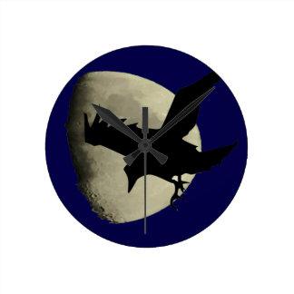 Horloge Ronde Raven volant à travers la lune