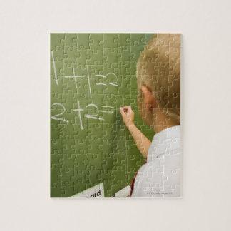 Jeune écriture caucasienne de garçon sur une salle puzzle