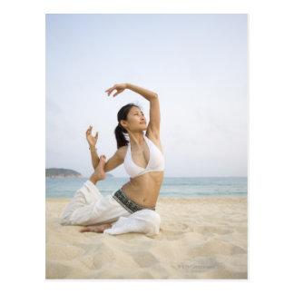 Jeune femme faisant le yoga sur la plage carte postale