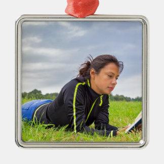 Jeune femme se situant dans le livre de lecture ornement carré argenté