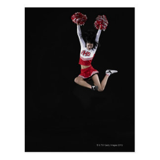 Jeune pom-pom girl femelle sautant dans l'entre le carte postale