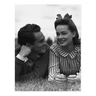 Jeunes couples se trouvant sur l'herbe carte postale
