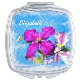 Jolies fleurs pourpres et clématite bleue avec le miroirs à maquillage