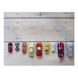 Jouez les voitures alignées dans une rangée sur le carte postale