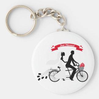 Juste jeunes mariés mariés sur la bicyclette tande porte-clé rond