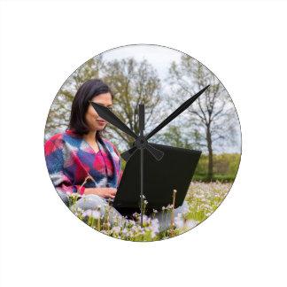 La femme s'assied avec l'ordinateur portable dans horloge ronde