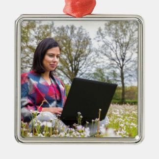 La femme s'assied avec l'ordinateur portable dans ornement carré argenté