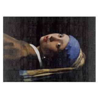 La fille avec une boucle d'oreille de perle par planche à découper
