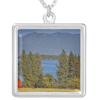 La grange rouge se repose le long du lac à tête collier
