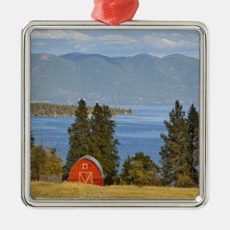 La grange rouge se repose le long du lac à tête ornement carré argenté