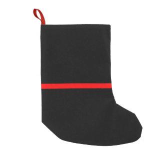 La ligne rouge mince symbolique sur le noir solide petite chaussette de noël