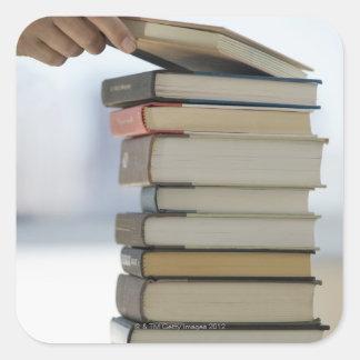 La main de l'homme prenant un livre d'une pile de sticker carré