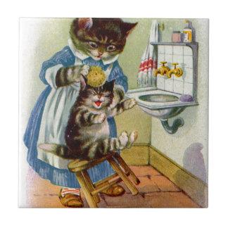 la maman de chat de minou des années 1930 lave son petit carreau carré