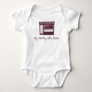 La maman vend la chemise de bébé de chaussures t-shirts