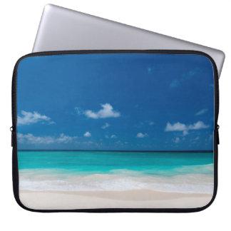 La plage blanche, le ciel bleu et la turquoise housse ordinateur portable