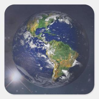 La terre de planète se levant au-dessus du soleil sticker carré