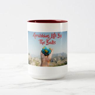 La vie de saisie par la tasse de boules