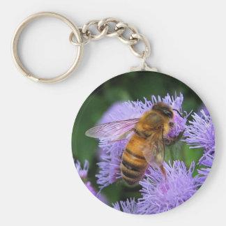 L'abeille sur l'Ageratum pourpre fleurit le porte Porte-clé Rond