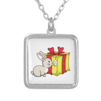 Lapin avec un cadeau pendentif carré