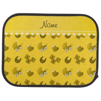 Le bavoir jaune nommé de bébé bloque des butins de tapis de sol