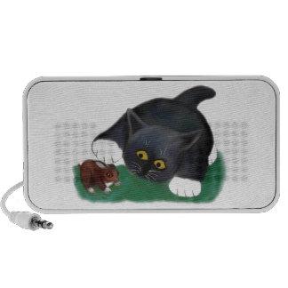 Le chaton noir et blanc de smoking choie son ami, haut-parleur portable