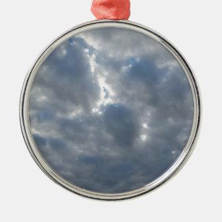 Le ciel avec les cumulonimbus et le soleil de ornement rond argenté