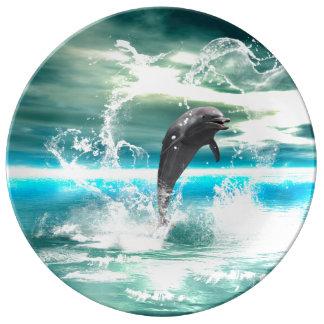 Le dauphin sautant en mer avec des vagues comme assiettes en porcelaine