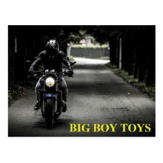 Le grand garçon de moto joue la carte postale