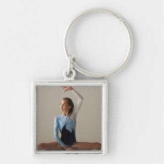 Le gymnaste féminin (12-13) exécutant se dédouble porte-clé carré argenté