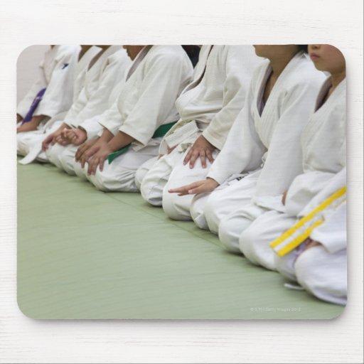 Le joueur de judo de l'enfant s'assied à une ligne tapis de souris