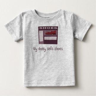 Le papa vend la chemise de bébé de chaussures t-shirts