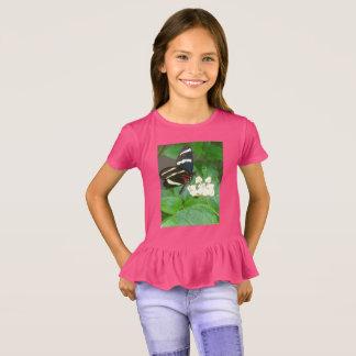 Le papillon des filles sur le T-shirt de fleurs