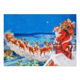 Le père noël et son renne sur le dessus de toit carte de vœux